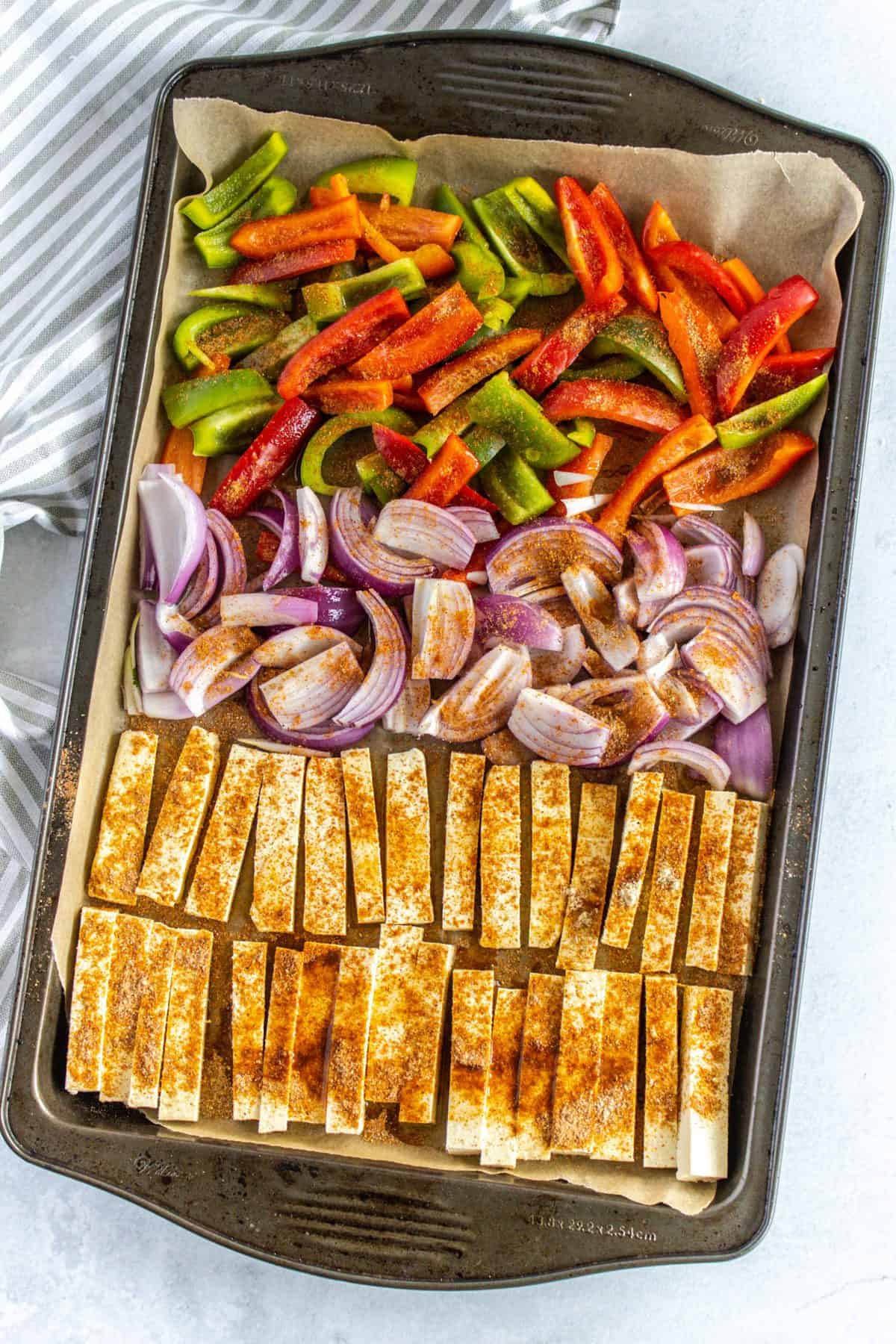 sliced tofu onion and bell pepper on a sheet pan
