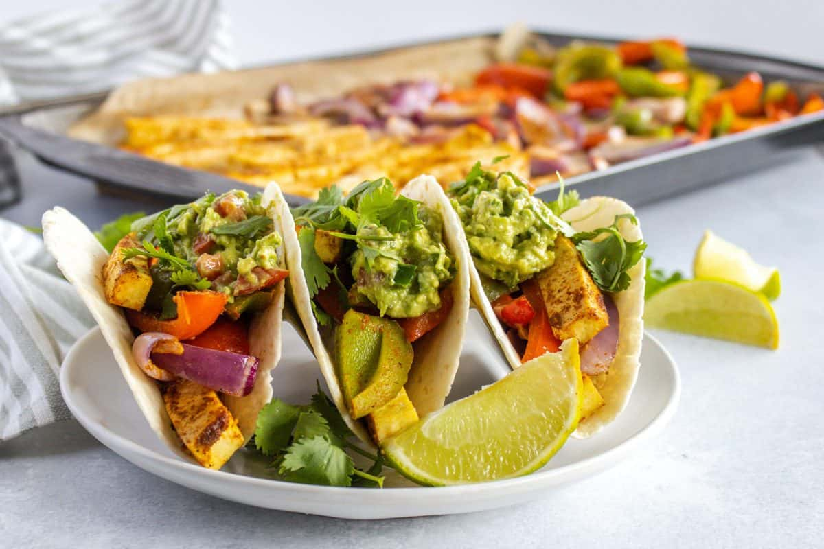 tofu fajitas with bell pepper and guacamole serve on white plate