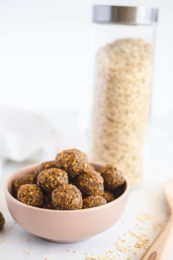 The energy balls on a smalls bowl  with oats in the background
