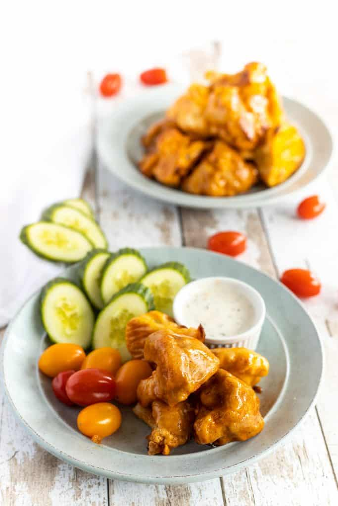 cauliflower wings in plate with sliced cucumber and cherry tomatoes