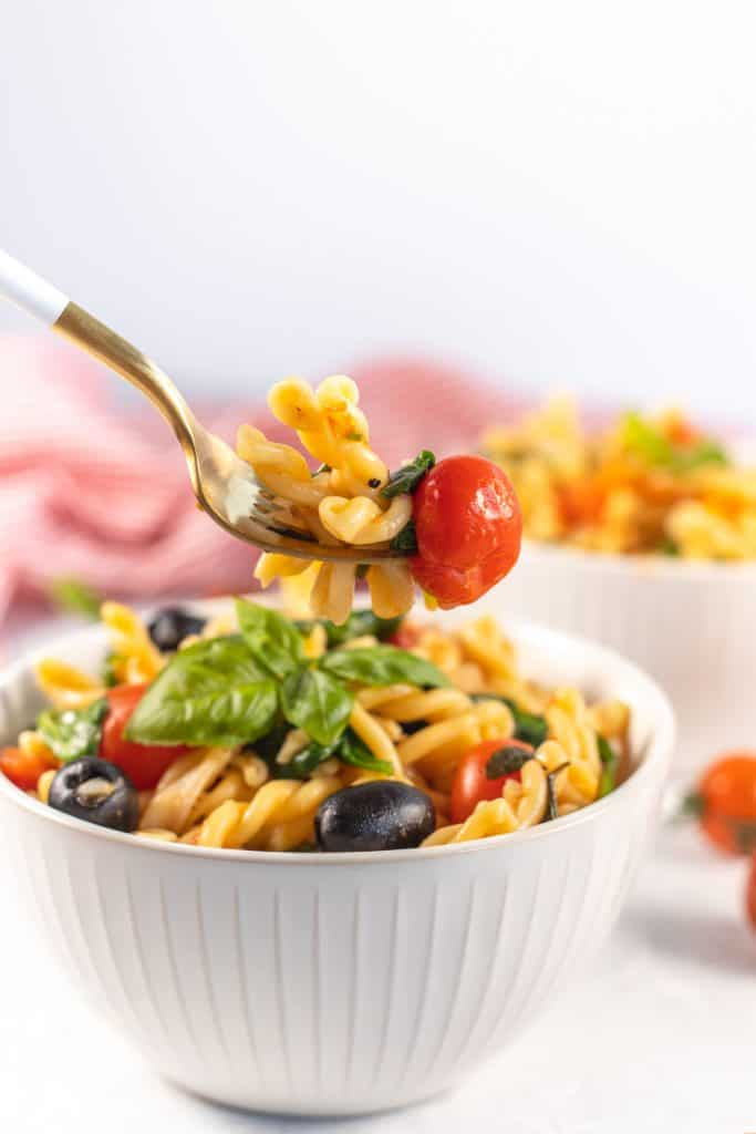 cooked pasta with cherry tomato on a fork