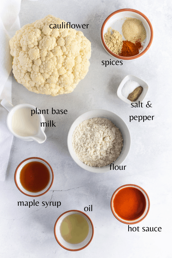 The ingredients you need to make this recipe, cauliflower, hot sauce, flour, spices, plant base milk, maples syrup and oil.