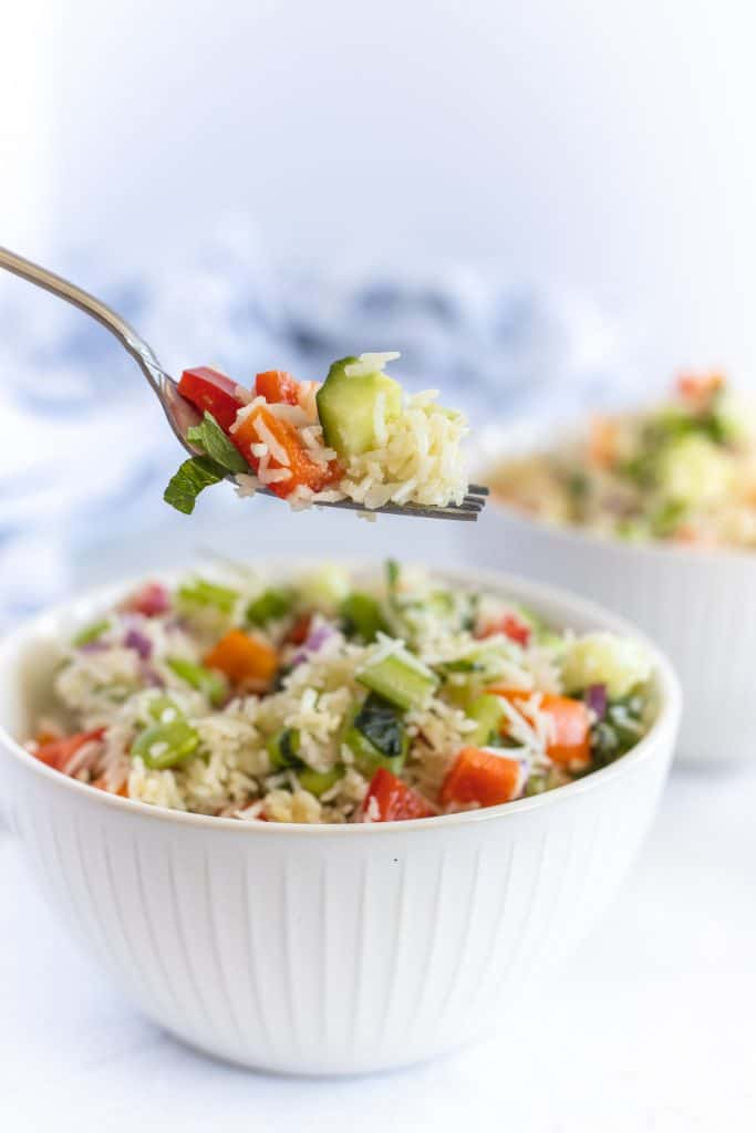 Bowl of basmati rice salad with a spoon full of salad