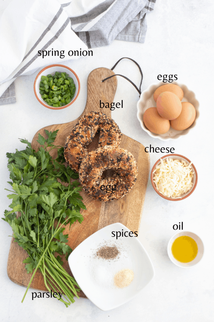 all the ingredients  on a wooden board you need to make the egg in a bagel hole