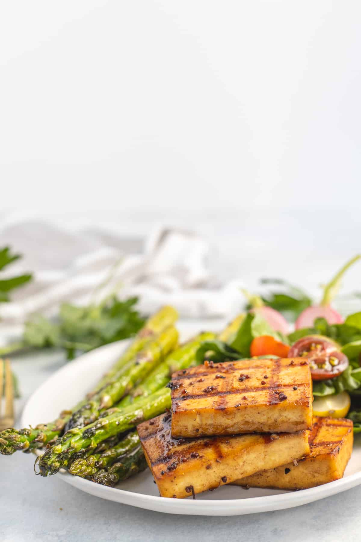 Marinated balsamic tofu in a plate with asparagus and salad