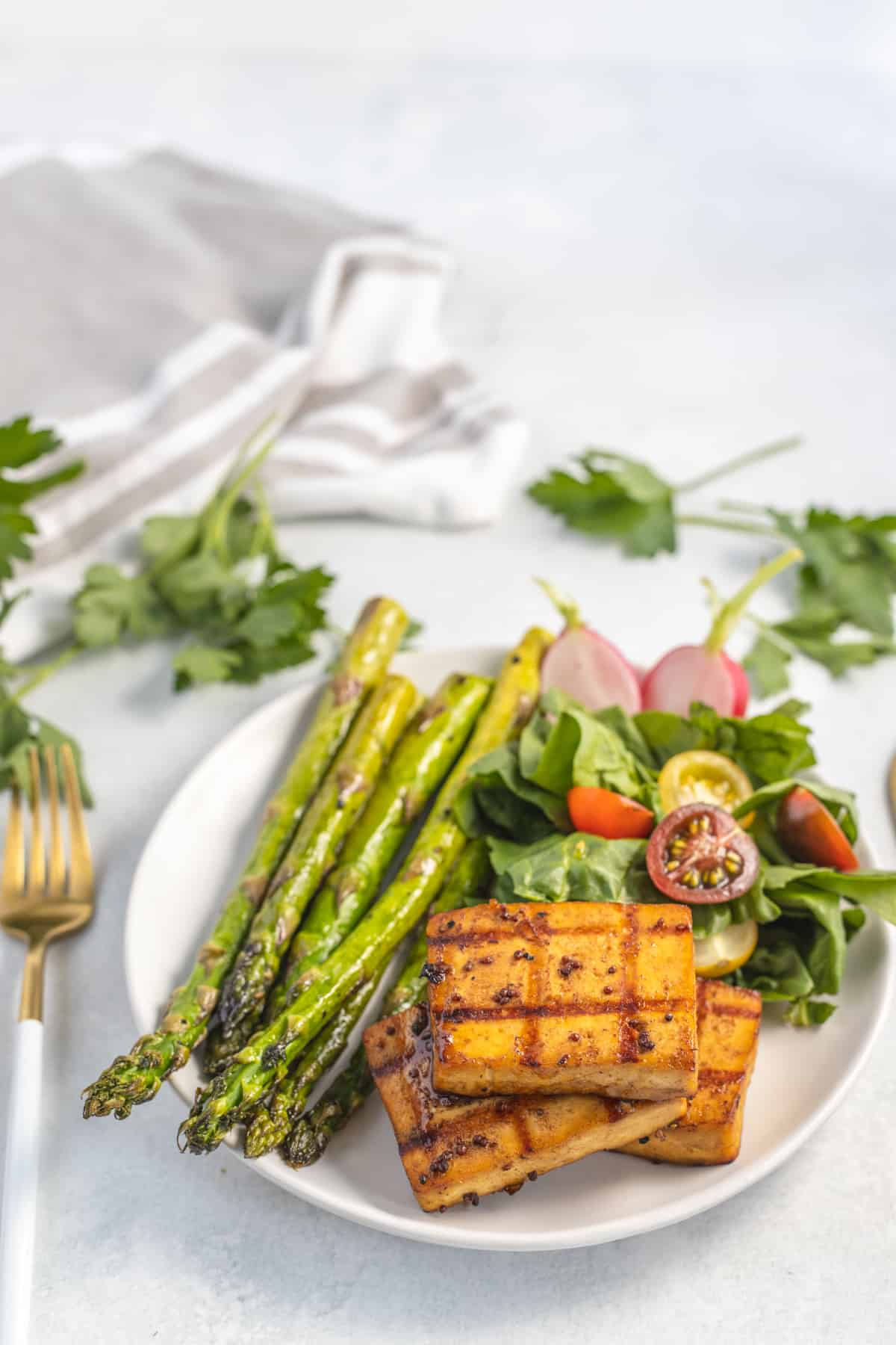 Cooked tofu  on a white plate with asparagus and salad